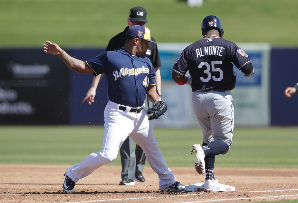 . Milwaukee Brewers pitcher Junior Guerra beats Cleveland Indians\' Abraham Almonte to the bag during a spring training baseball game, Monday, Feb. 26, 2018, in Maryvale, Ariz. (AP Photo/Carlos Osorio)