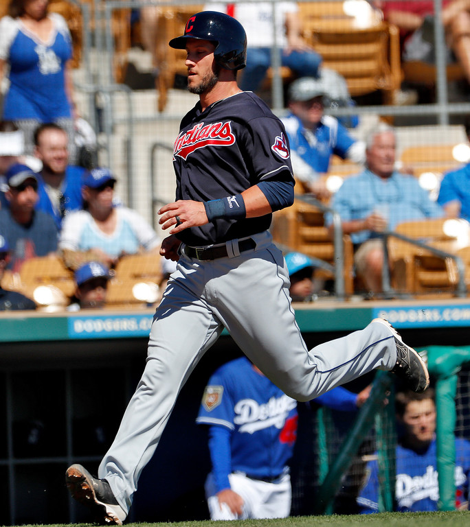 . Cleveland Indians\' Yan Gomes scores on an RBI-base hit by Yonder Alonso during the first inning of a spring training baseball game against the Los Angeles Dodgers, Monday, March 5, 2018, in Phoenix. (AP Photo/Matt York)