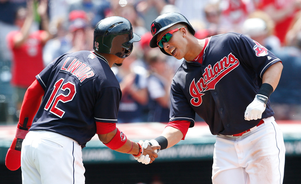 . Cleveland Indians\' Michael Brantley, right, gets congratulations from Francisco Lindor after hitting a two run home run off Seattle Mariners relief pitcher Casey Fien during the third inning in a baseball game, Sunday, April 30, 2017, in Cleveland. (AP Photo/Ron Schwane)