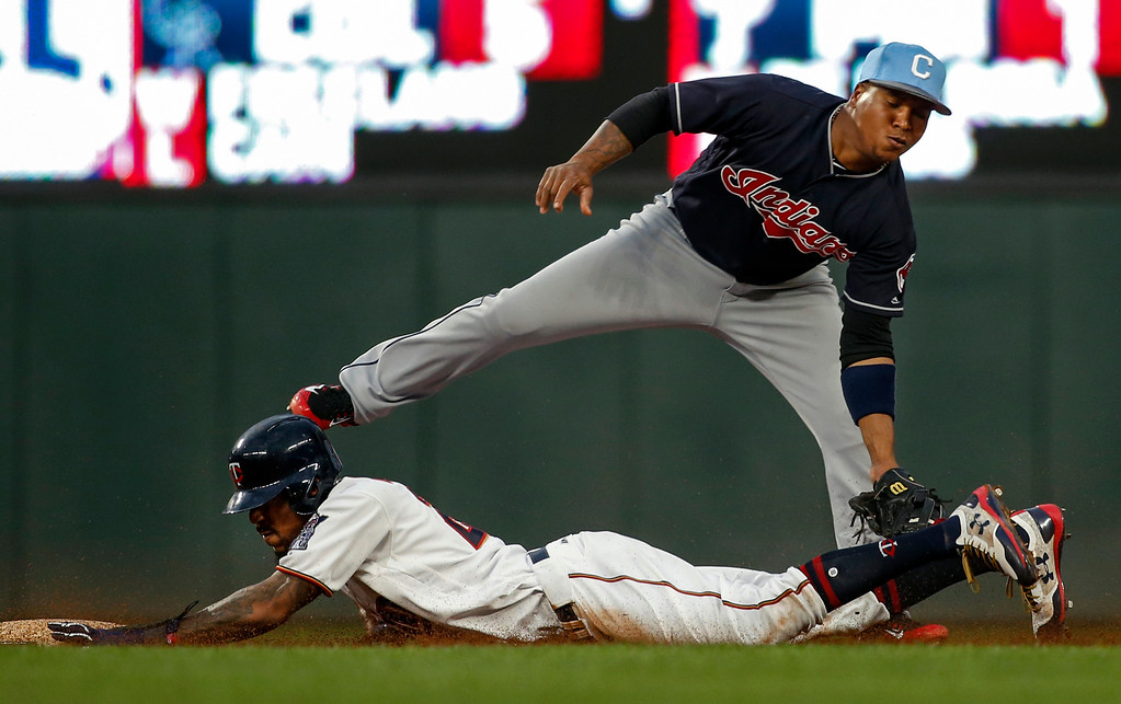 . Minnesota Twins\' Byron Buxton, bottom, steals second ahead of the tag by Cleveland Indians second baseman Jose Ramirez in the third inning of the second baseball game of a doubleheader Saturday, June 17, 2017, in Minneapolis. Initially called out, the call was reversed after review. (AP Photo/Bruce Kluckhohn)