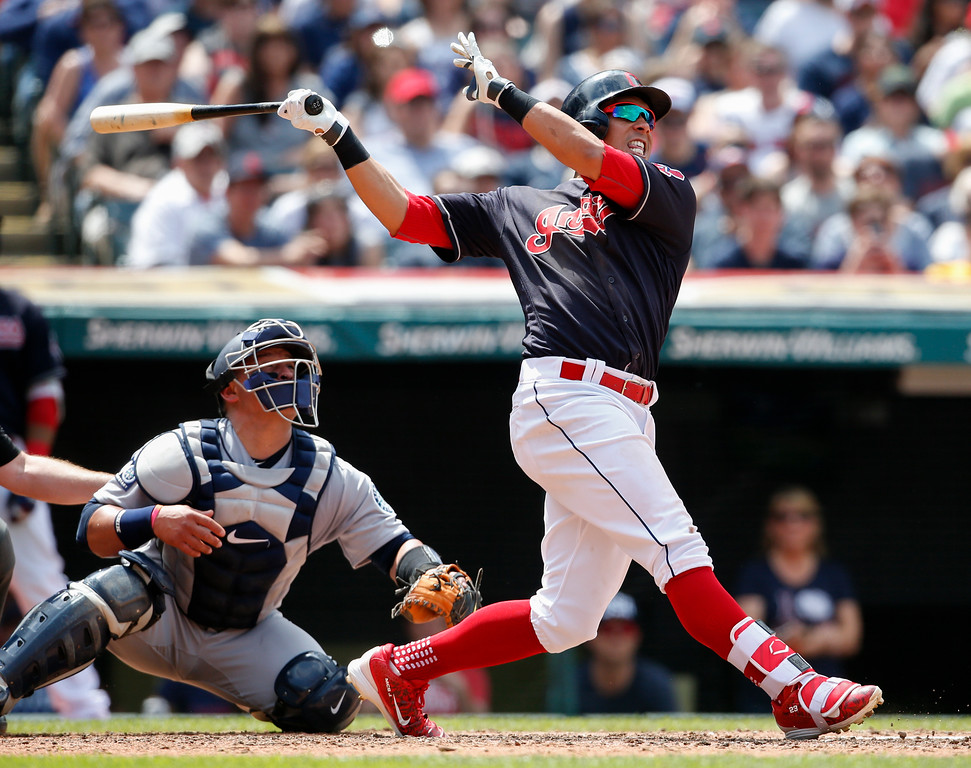 . Cleveland Indians\' Michael Brantley watches his two-run home run as Seattle Mariners catcher Carlos Ruiz looks on during the third inning in a baseball game, Sunday, April 30, 2017, in Cleveland. (AP Photo/Ron Schwane)