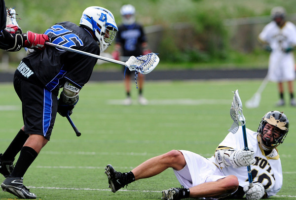 """The Monarch Coyote's Nathan Puldy (10) scores and takes a hard check from Alexander Dawson's Akil Baghat (25) during their game at Monarch High on Wednesday April 25, 2012.  For more photos of the game go to  <a href=""""http://www.bocopreps.com"""">http://www.bocopreps.com</a><br /> Photo by Paul Aiken"""