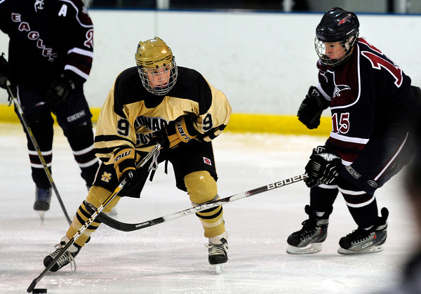 """Monarch High School Hockey Team's Walker Harris (9) skates he puck Dakota Ridge's Blake Davies (15) during their game at the Boulder Valley Ice rink in Superior on Monday January 23, 2012. For more photos and a recap of the game go to  <a href=""""http://www.bocopreps.com"""">http://www.bocopreps.com</a>. <br /> Photo by Paul Aiken"""