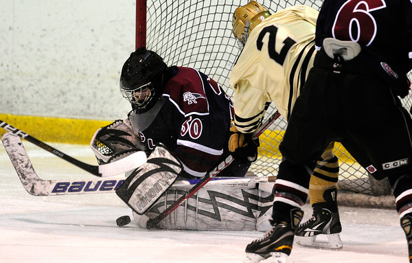 """Monarch High School Hockey Team's Noah Zimmerman (2) jams the puck in against Dakota Ridge's Goalie Cody Giles (30) during their game at the Boulder Valley Ice rink in Superior on Monday January 23, 2012. For more photos and a recap of the game go to  <a href=""""http://www.bocopreps.com"""">http://www.bocopreps.com</a>. <br /> Photo by Paul Aiken"""