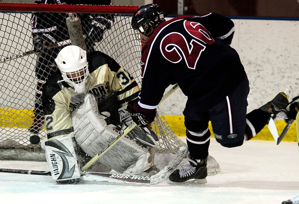 """Monarch High School Hockey Team's Goalie Akira Kyle (32) defects a shot by Dakota Ridge's Zach Czarnecki (26)  during their game at the Boulder Valley Ice rink in Superior on Monday January 23, 2012. For more photos and a recap of the game go to  <a href=""""http://www.bocopreps.com"""">http://www.bocopreps.com</a>. <br /> Photo by Paul Aiken"""
