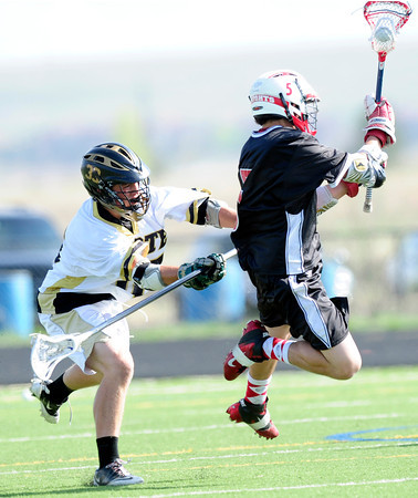 "Monarch High School's Dane Muller (15) tries to stop a shot by Fairview High School's Chris Robinson (5) during their game at Monarch High School on Tuesday April 10, 2012<br /> For more photos of the game go to  <a href=""http://www.bocopreps.com"">http://www.bocopreps.com</a>.<br /> <br /> Photo by Paul Aiken / The Camera"