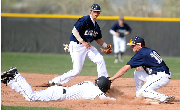 """Legacy High School's Dillon Bollig (10) puts a pickoff tag on Monarch High School's Brian Wood (6) during their game Tuesday afternoon at Monarch High School April 17, 2012. Wood got into base safely. <br /> For more photos of the game go to  <a href=""""http://www.bocopreps.com"""">http://www.bocopreps.com</a><br /> Photo by Paul Aiken   /  The Camera"""