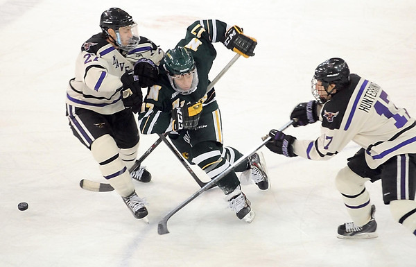 Northern Michigan's John Siemer is checked off the puck by Minnesota State's Brett Stern as Minnesota State's Michael Huntebrinker goes for the puck during the first period Saturday at the Verizon Wireless Center in Mankato. Pat Christman