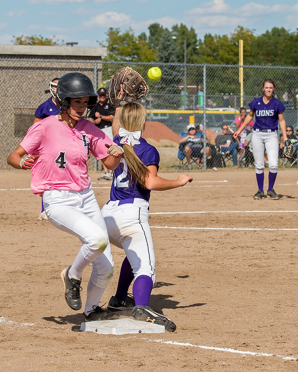 . Loveland\'s Blair Bernhardt (4) beats the throw to first base as Mountain View\'s Madison Langman (12) stretches to make the catch Saturday afternoon Sept. 17, 2016 during a 5-0 Indians victory on the Mountain Lions home field in Loveland. (Photo by Michael Brian/Loveland Reporter-Herald)