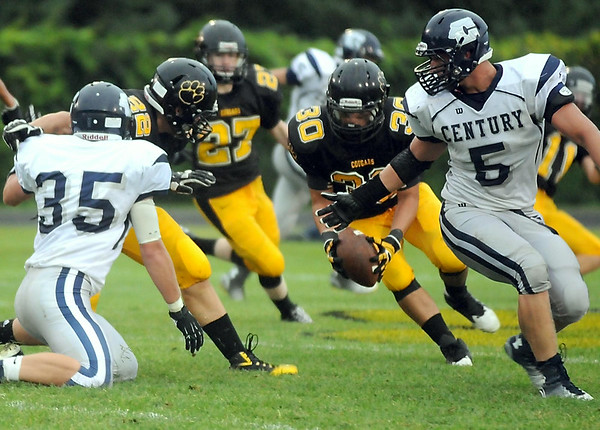 Mankato East's Chris Sadaka (30) scoops up a Rochester Century fumble during the first half Friday at Wolverton Field. Photo by Pat Christman