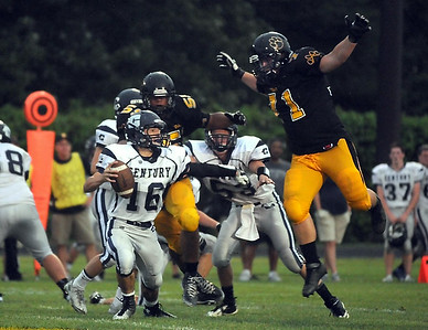 Mankato East's Cory Weston leaps toward Rochester Century quarterback Miguel Benjamin during the first half Friday at Wolverton Field. Photo by Pat Christman