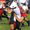 Pat Christman <br /> Mankato West's Charlie Schwartz brings down Mankato East quarterback Nick Seiler during the first half Friday at Blakeslee Stadium.