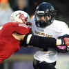 Pat Christman <br /> Mankato West's Isaac Weber wraps up Mankato East's Cooper Wolfe during the first half Friday at Blakeslee Stadium.