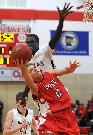 Pat Christman<br /> Mankato East's Gorg Alhag tries to block a shot by Mankato West's Jake Makela during the first half Saturday at the West gym.