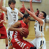 Pat Christman<br /> Mankato West's Braedan Myers' route to the basket is blocked by Mankato East's Nic Seiler, right, and Sam Ahrens during the first half Saturday.