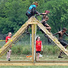 Mud covered runners climb a net obstacle Saturday. Photo by Pat Christman