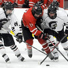 Pat Christman<br /> Mankato West's Christian Klemme is checked off the puck by New Prague's Seth Kriha (24) and Dan Beckius (32) during the second period of their Section 1A championship game Thursday at the Rochester Recreation Center.
