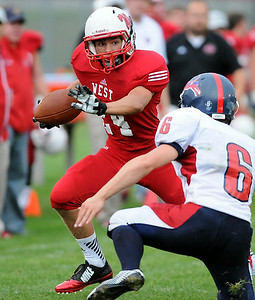 Mankato West's Carter Burroughs dodges an Albert Lea defender during a touchdown run in the first half Thursday at Todnem Field. Photo by Pat Christman