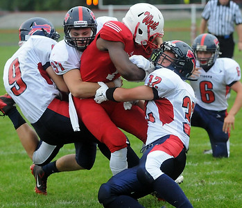 Mankato West running back Travon Jones pushes through a trio of Albert Lea defenders for a first half touchdown Thursday. Photo by Pat Christman