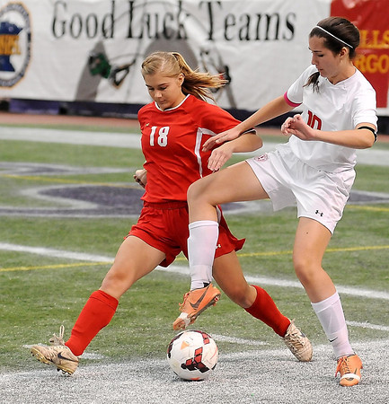 Mankato West's Abbie Harris and Benilde-St. Margaret's Elizabeth Ambre try to control the ball during State Class A semifinal action at the Metrodome on Monday.