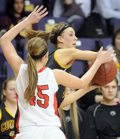 Pat Christman<br /> Mankato East's Taylor Karge passes away from Mankato West's Hannah Hastings during the second half Tuesday at Bresnan Arena.