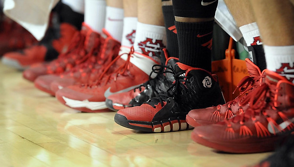 Pat Christman<br /> A lone pair of black shoes interrupts the line of red ones on the Mankato West bench during the boys basketball game Tuesday.