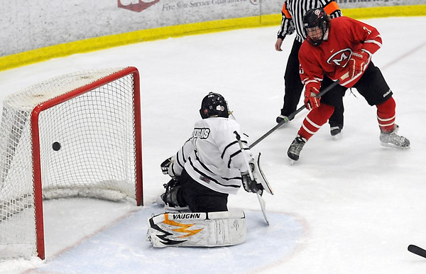 Pat Christman<br /> Mankato West's Nick Campbell puts a shot past Mankato East/Loyola goalie Will Behsman during the first period Tuesday at All Seasons Arena.