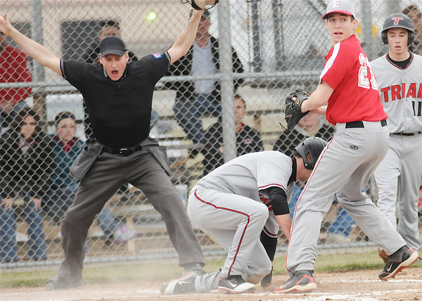 Effingham's Drew Levitt stands in front of home plate as a runner from Troy Triad scores behind him on a wild pitch.