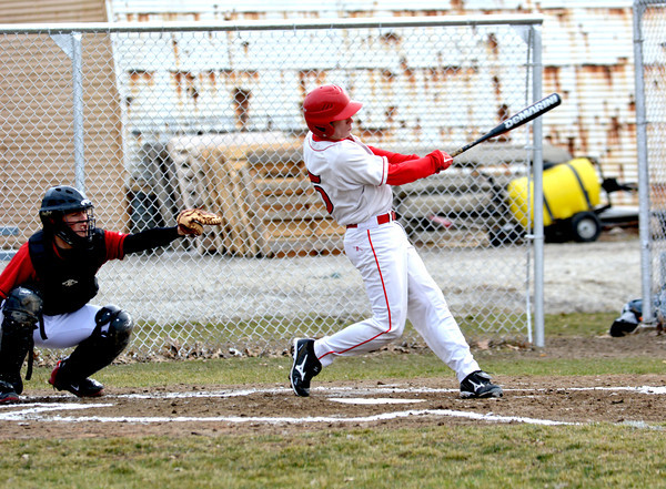 Neoga's Matt Kingery swings through a pitch and fouls it off while North Clay's Lawson Britton catches behind him.