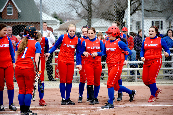 St. Anthony's Makayla Walsh (center, helmet) is greeted by teammates after a home run during a 24-5 loss to Cumberland.