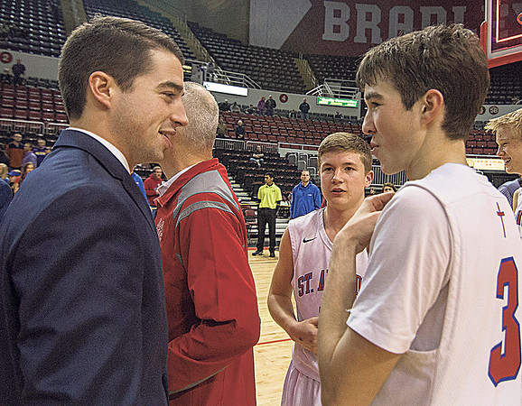 St. Anthony assistant coach Curran Walsh, left, and point guard and brother Cade Walsh, right, talk prior to receiving their Class 1A state championship medals following their 49-46 win over Okawville.