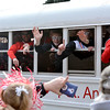 St. Anthony's Jack Nuxoll (center) waves to the crowd alongside coaches and teammates on the bus during the St. Anthony Bulldogs' state championship parade through town.