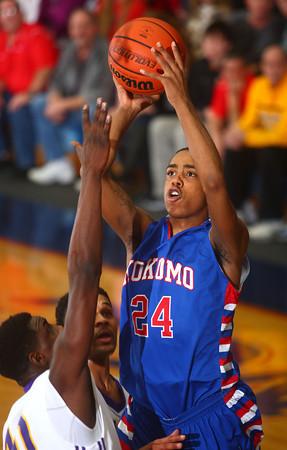 3-7-14<br /> Kokomo vs. Marion basketball<br /> Kokomo's Mykal Cox jumps above Marion's defense for a shot.<br /> KT photo | Kelly Lafferty