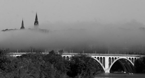 Gothic spires of Georgetown University, with marathoners crossing the Key Bridge in the foreground