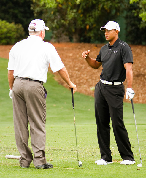 Tiger Woods talks with Mark O'Meara on the practice range at the 2012 Masters