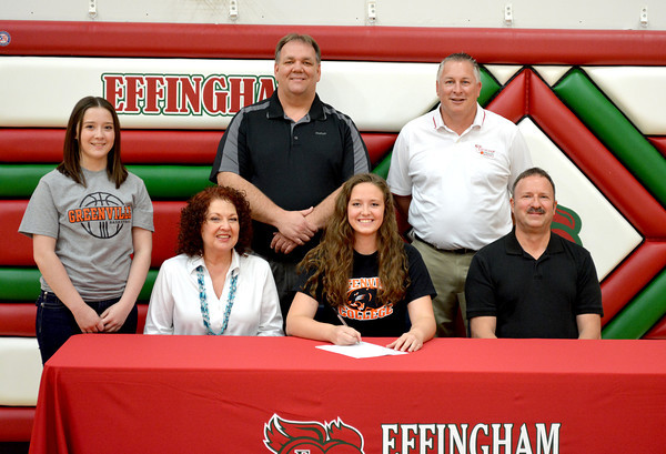 Effingham's Lauren Stephenson (center right) had her commitment ceremony to play basketball at Division III's Greenville College Wednesday afternoon. On the far right is her father Terry Stephenson, with her sister Lindsey Stephenson on the far left and her mother Jeanine Stephenson in the middle left. Back row, from left: Central Illinois Storm coach Barry Wolfe, Effingham girls basketball coach Jeff Schafer.