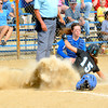 Cumberland's Audrey Casey (15) slides safely into home plate and kicks up a cloud of dust in front of Danville Schlarman catcher Hailee Powell as the ball kicks away from her in Cumberland's 4-0 win at the Class 1A Cumberland Regional.