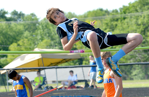 Cumberland's Trevor Beard skies over the bar in the high jump while  a member of the Flora Wolves looks on behind him at the Class 1A Newton Sectional.