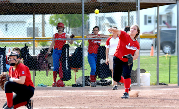 Negoa third baseman Allison Posten (right) fires a ball to first across the diamond while Neoga pitcher Bayley Neece (left) ducks under the throw against St. Anthony in the National Trail Conference tournament.