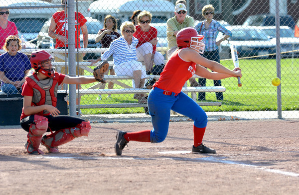 St. Anthony's Paige Koester (right) attempts a slap hit while Neoga catcher Kristen Albin remains in her crouch behind her at the National Trail Conference tournament.
