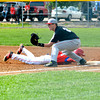 Effingham first baseman Lane Koenig awaits a throw to first while St. Anthony's Neil Williams dives back to the bag.