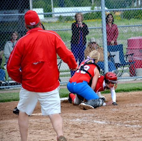 St. Anthony catcher Hunter Niebrugge blocks the plate and tags out Effingham runner Katie Roberts in the ninth inning of game one of the City Series, while Effingham assistant coach Jeff Tonn looks on in the foreground.