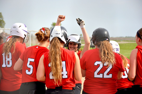 Neoga's Amber Potter (center) raises her arms in celebration after hitting a grand slam against Stew-Stras/Windsor.