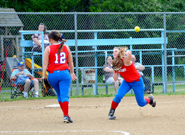 St. Anthony shortstop Jenna Woltman (right) fires a ball toward first while Kristen Schuette (12) walks back to third against St. Elmo/Brownstown.