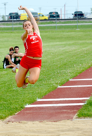 Effingham's Claire Niebrugge jumps into the sand during the long jump at the Apollo Conference track meet.