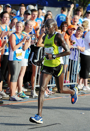 Globe/T. Rob Brown<br /> Winner Benson Chesang, of Lawrence, Kan., heads toward the finish line of the half-marathon as the crowd cheers Saturday morning, May 19, 2012, during the Joplin Memorial Run in downtown Joplin.