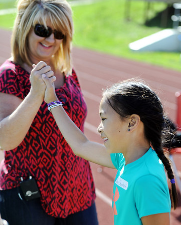 Globe/T. Rob Brown<br /> Haven Shepherd, a Carthage Elementary School third grader, is congratulated by her adopted mother, Shelly Shepherd, after finishing a race during a school track meet Wednesday morning, May 9, 2012, at K.E. Baker Stadium in Carthage. Young Shepherd, who was adopted by the Carthage family, is originally from Vietnam. She lost her legs during an explosion when she was a 1-year-old.