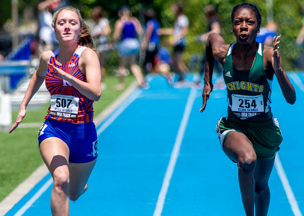 Newton's Alex Haarman (left) races beside Metro-East Lutheran's Jaria Hardaway during the 100-meter dash at the state track preliminary meet. Haarman finished with a time of 13.52.