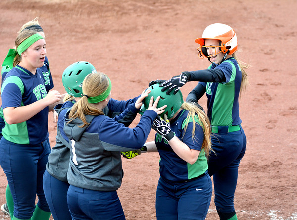 Windsor/Stew-Stras' Katie Greuel (center) is congratulated at home by teammates, led by Becca Schlechte (right), after hitting a home run against South Central during the National Trail Conference Tournament.