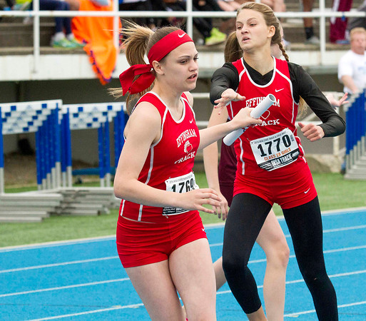 Effingham's Kiyah Kuhlman (left) gets the exchange from Kaylee Phillips (right) going into the third leg of the 4x400-meter relay at the Class 2A state track preliminary meet.